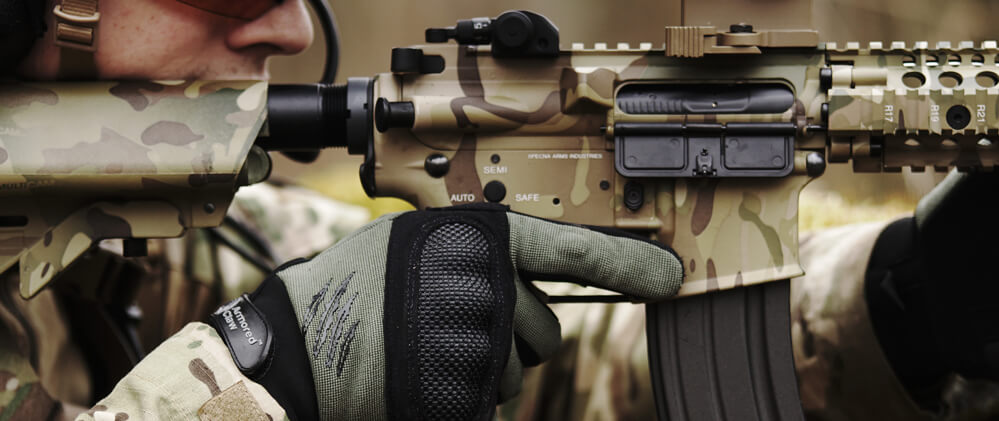 Man aiming through the scope of an Airsoft rifle